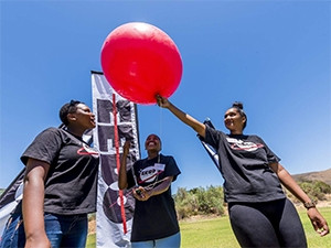 STEM candidates release a weather balloon attached to a CricketSat.