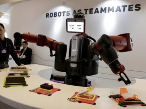 One of Rethink Robotics' Baxter robots picks up a business card during a display at the World Economic Forum in Dalian, China in September 2015.