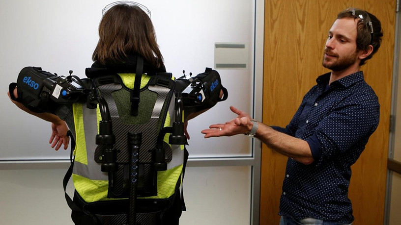 Marty Smets, Ford ergonomics engineer, demonstrates the exoskeleton.