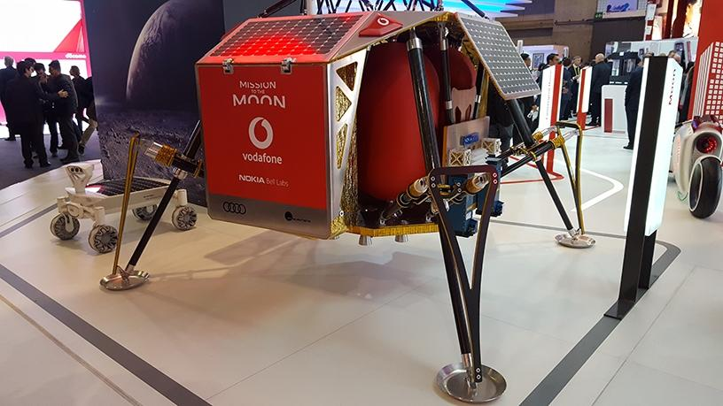 The Autonomous Landing and Navigation Module on display at Vodafone's MWC booth, with the Audi lunar quattro rover in the background.