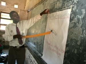A teacher explains to students how mosquitoes infect people with malaria. CREDIT: WHO/S. Hollyman.