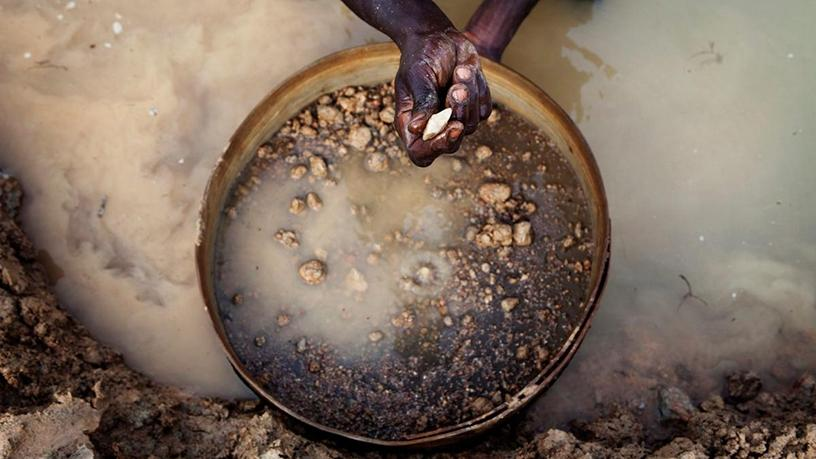 A miner pans for diamonds in Koidu, eastern Sierra Leone.