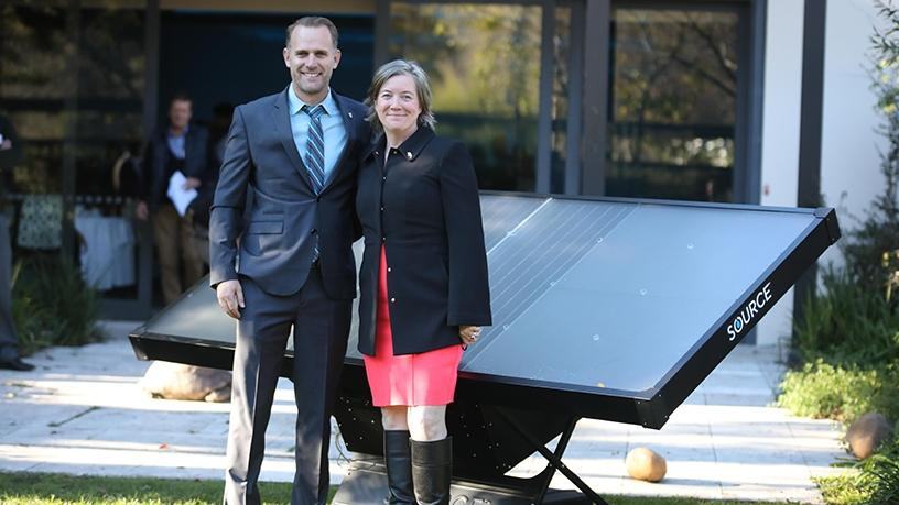 Cody Friesen, Zero Mass Water CEO, and US consul general, Virginia Blaser, in front of an array of SOURCE Hydropanels at the Vineyard Hotel in Cape Town.